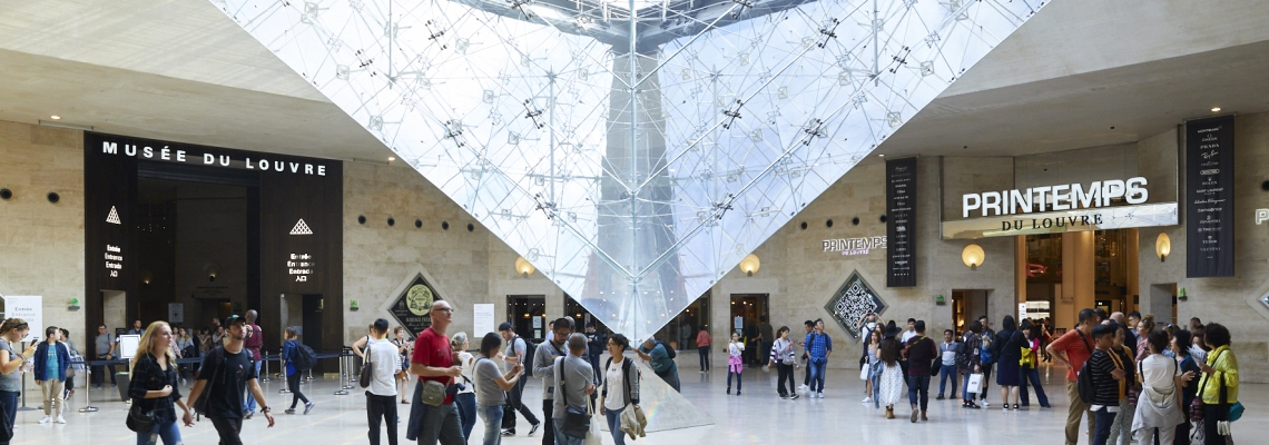 Customers stroll across the Rivoli and Carrousel shopping alley, with leoh Ming Pei's inverted pyramid in the backround, in the Carrousel du Louvre shopping centre